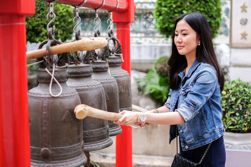 Kvinna som ringer en klocka i en buddistisk tempel royaltyfria bilder