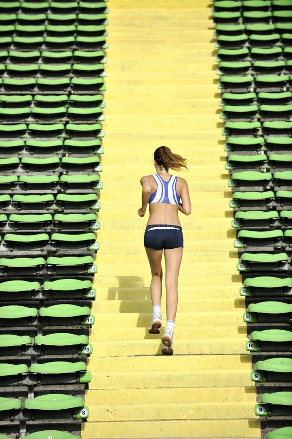 Kvinna som rustar på friidrottstadionen fotografering för bildbyråer