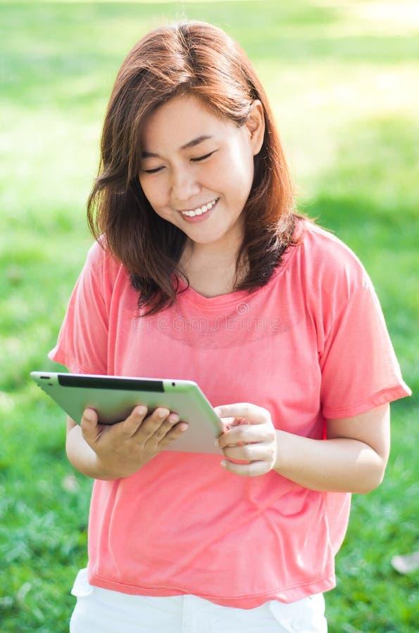 Kvinna som rymmer den Digital minnestavlan fotografering för bildbyråer