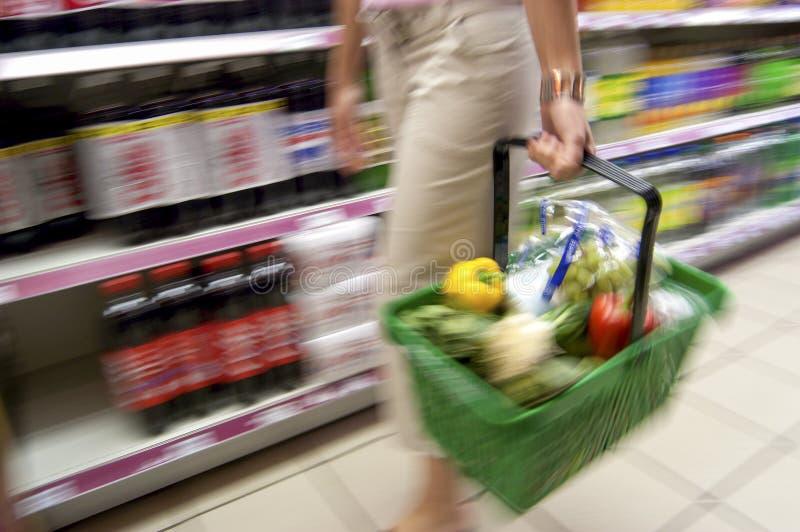 Kvinna som rymmer den fulla shoppingkorgen längs sodavattengången i Supermark royaltyfri bild