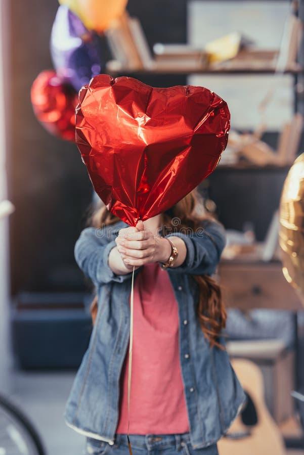 Kvinna som rymmer den röda ballongen och anseende i smutsigt rum efter parti fotografering för bildbyråer