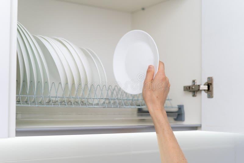 Kvinna som rymmer den rena och vita plattan nära dishware i köksskåp arkivbilder