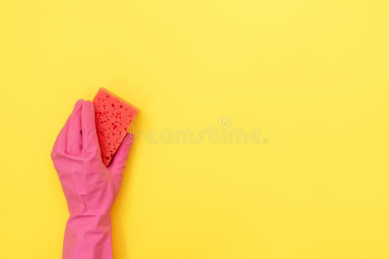 Kvinna som rymmer den rosa svampen för tvätt i hennes händer mot gul bakgrund royaltyfria bilder