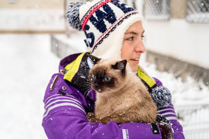 Kvinna som rymmer den Siamese katten i snö arkivfoton