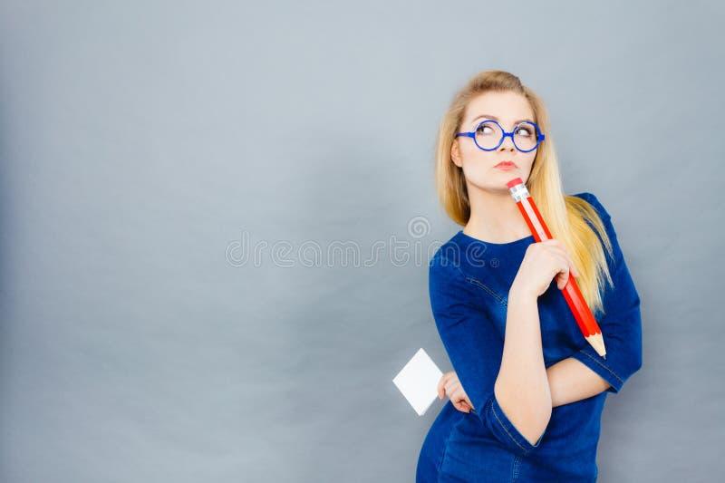 Kvinna som rymmer den stora överdimensionerade blyertspennan som tänker om något arkivbild