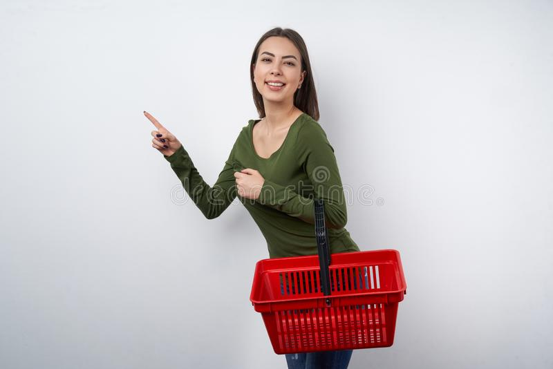 Kvinna som rymmer den tomma shoppa korgen som pekar för att sid royaltyfria bilder