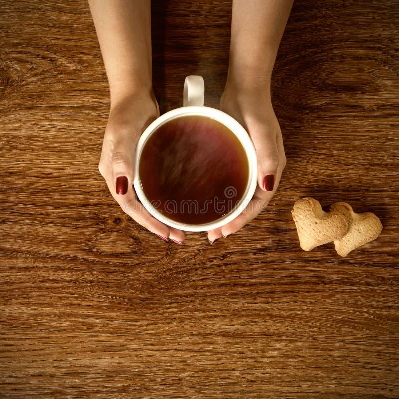Kvinna som rymmer den varma kopp te med kakor på trätabellen royaltyfri foto