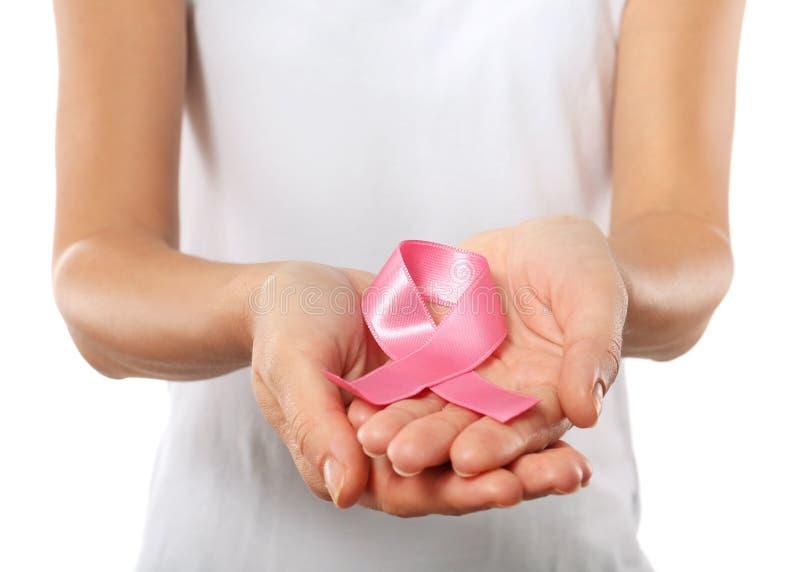 Kvinna som rymmer det rosa bandet p? vit bakgrund, closeup Rosa band p? corkboard arkivfoton