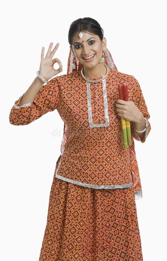 Kvinna som rymmer en Dandiya på Navratri och gör det ok tecknet arkivbild
