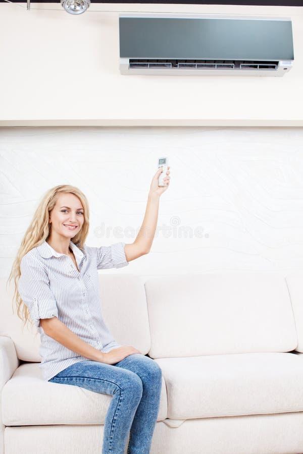 Kvinna som rymmer en fjärrkontrollluftkonditioneringsapparat royaltyfria bilder