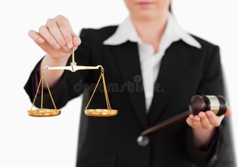 Kvinna som rymmer en gavel och scales av rättvisa royaltyfri foto