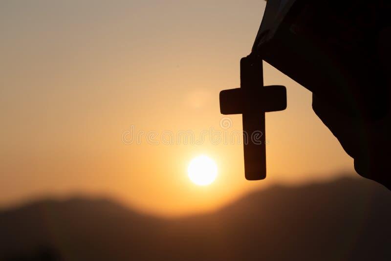 Kvinna som rymmer en helig bibel och ett kors i hennes händer och ber i morgonen Händer vikta i bön på en helig bibel i kyrka royaltyfri bild
