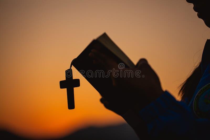 Kvinna som rymmer en helig bibel och ett kors i hennes händer och ber i morgonen Händer vikta i bön på en helig bibel i kyrka royaltyfria foton