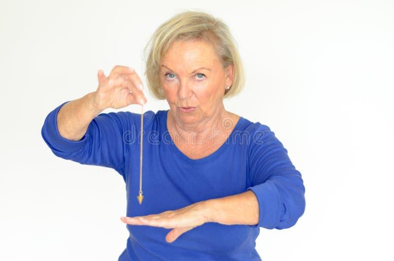 Kvinna som rymmer en klockpendel över hennes hand arkivfoto