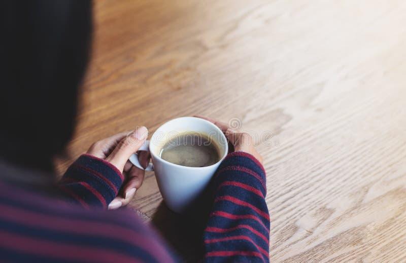 Kvinna som rymmer en kopp av varmt kaffe, vintersäsong royaltyfri fotografi