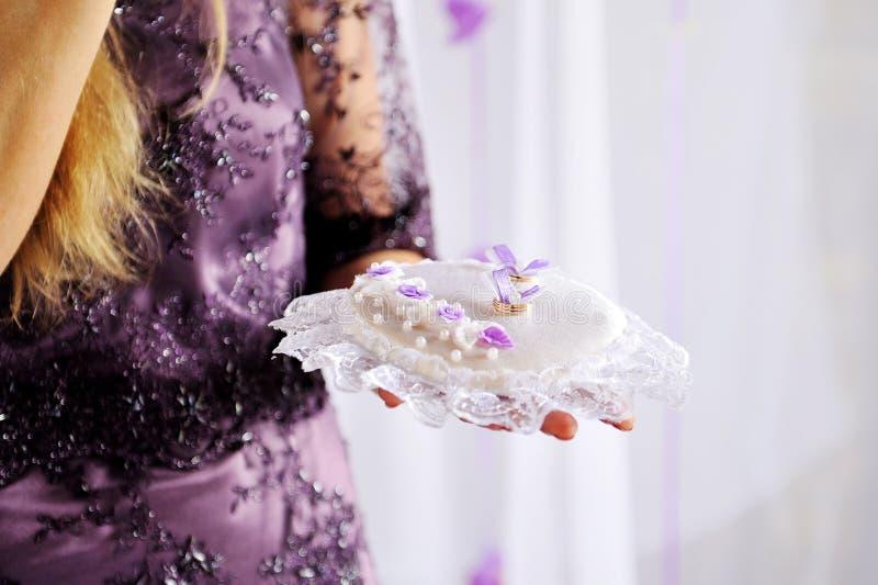 Kvinna som rymmer en kudde med guld- cirklar på bröllopceremoni fotografering för bildbyråer