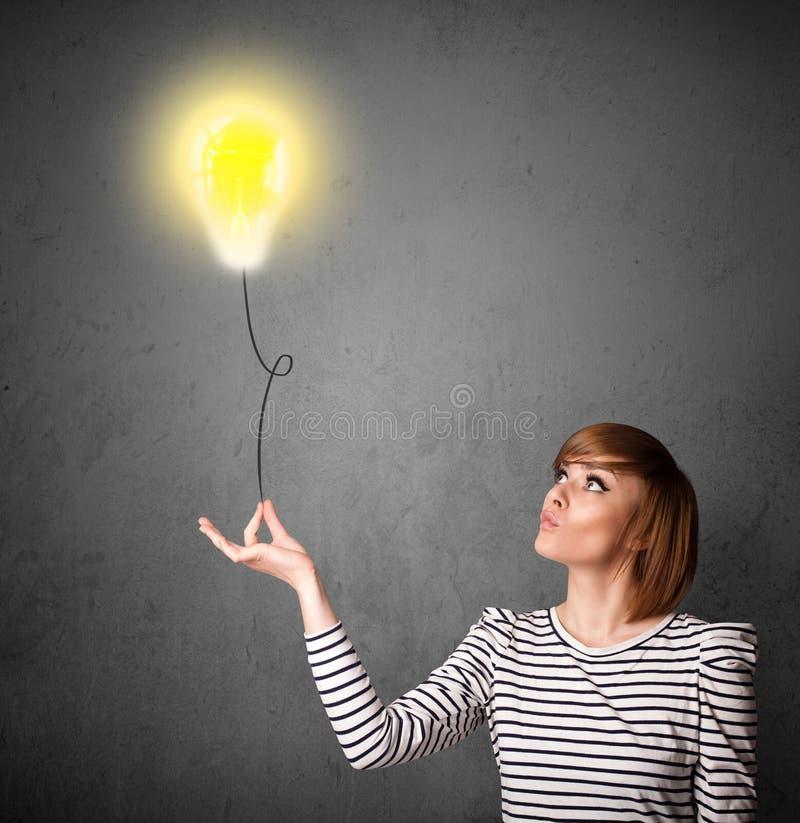Kvinna som rymmer en lightbulbballong royaltyfri foto
