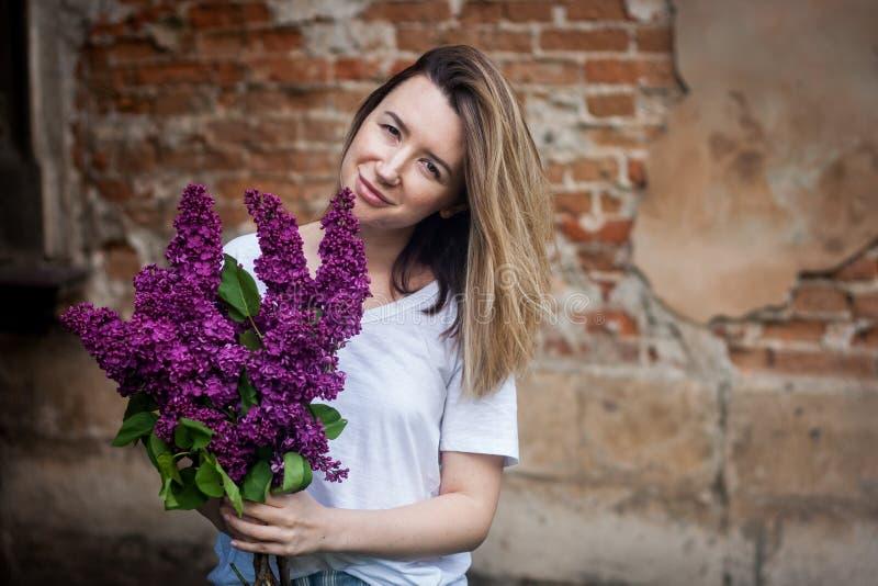 Kvinna som rymmer en livlig grupp av lila blommor mot tegelstenväggen royaltyfri foto