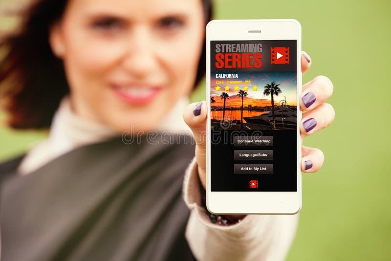 Kvinna som rymmer en mobiltelefon i handen med tryckning av videoen app i skärmen royaltyfria foton