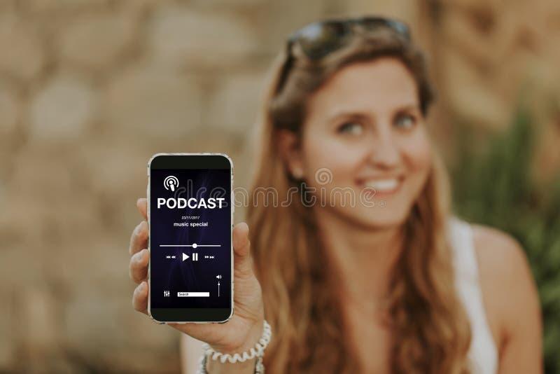 Kvinna som rymmer en mobiltelefon och visar den, med en podcast app i skärmen royaltyfri fotografi