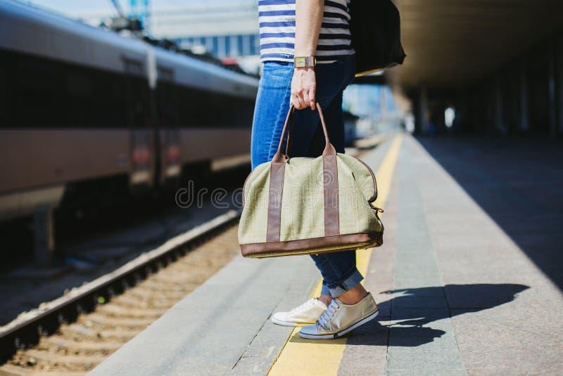 Kvinna som rymmer en påse på en järnvägsstation royaltyfria foton