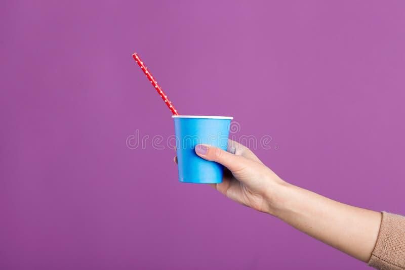 Kvinna som rymmer en pappers- kopp med röret som isoleras över purpurfärgad bakgrund arkivfoton