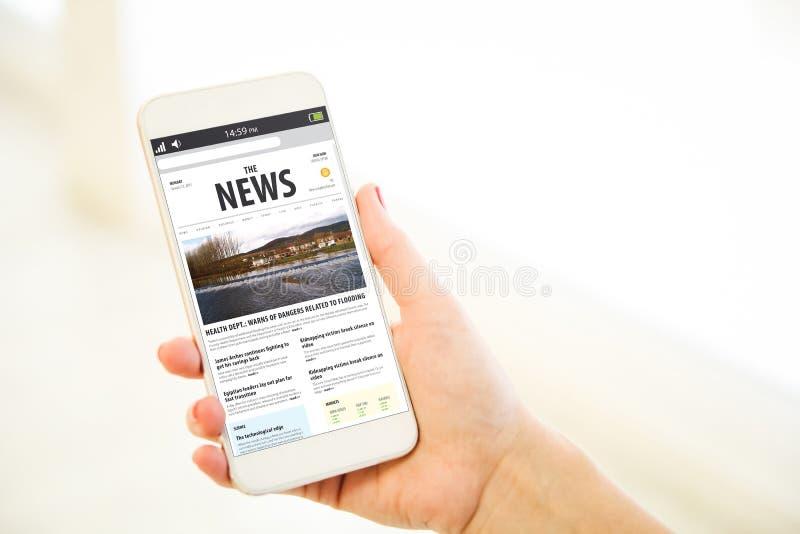 Kvinna som rymmer en rosa nyheterna för guldmellanrumssmartphone royaltyfri fotografi