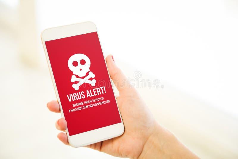 Kvinna som rymmer en rosa varning för virus för guldmellanrumssmartphone royaltyfri bild