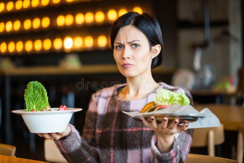 Kvinna som rymmer en sallad och en hamburgare Kvinna som väljer mellan sunt och sjukligt äta arkivfoto