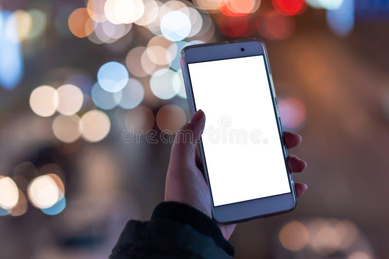 Kvinna som rymmer en smartphone med den tomma skärmen royaltyfri fotografi