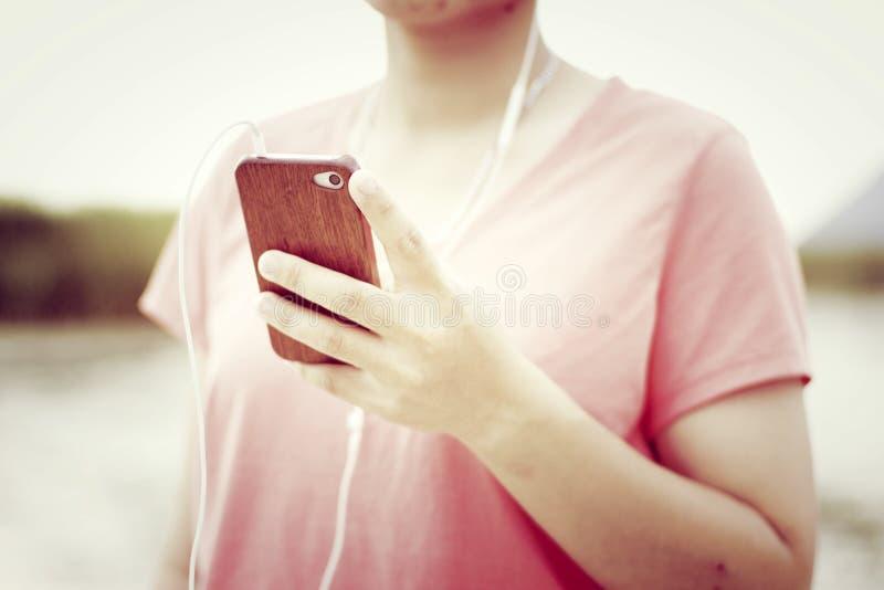 Kvinna som rymmer en smartphone som lyssnar till musik royaltyfri fotografi