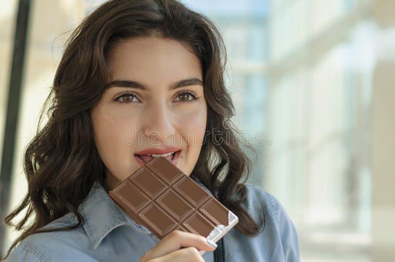 Kvinna som rymmer en stång av choklad royaltyfri bild