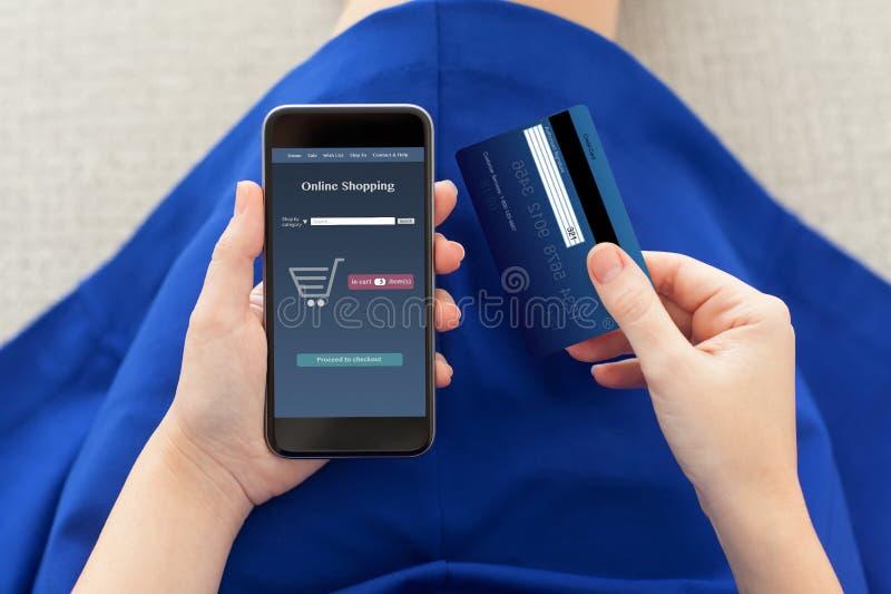 Kvinna som rymmer en telefon med online-shopping och kreditkorten arkivfoton