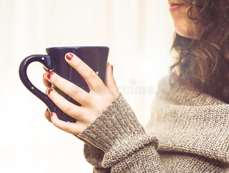 Kvinna som rymmer en varmt kopp kaffe eller te i morgonsolljuset arkivfoto