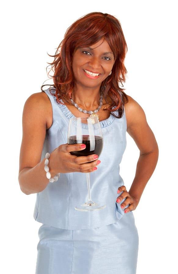 Kvinna som rymmer ett exponeringsglas av rött vin arkivfoto