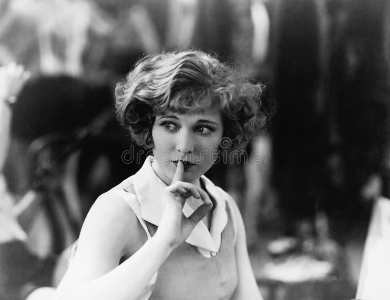 Kvinna som rymmer ett finger främst av hennes mun som signalerar för att vara tystnad (alla visade personer inte är längre uppehä royaltyfri bild