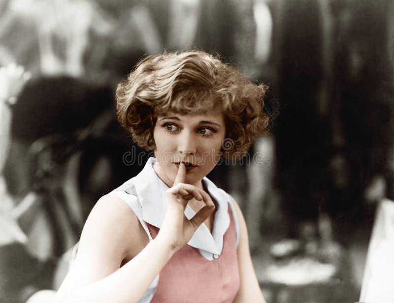 Kvinna som rymmer ett finger främst av hennes mun som signalerar för att vara tystnad (alla visade personer inte är längre uppehä arkivfoton