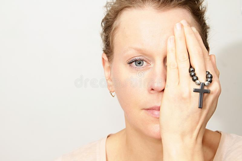 Kvinna som rymmer ett kors i henne händer arkivfoto