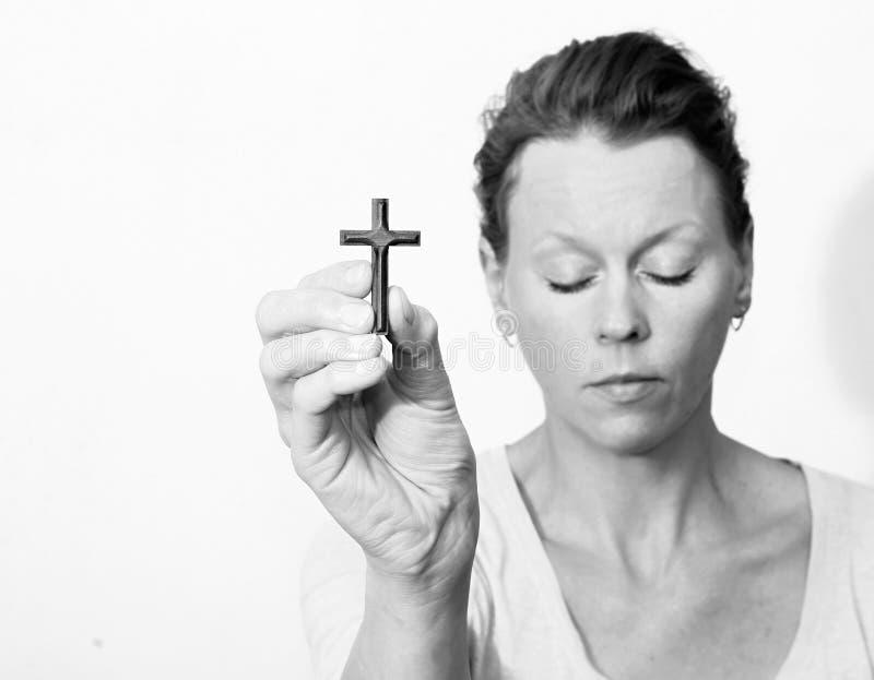 Kvinna som rymmer ett kors i henne händer royaltyfri fotografi