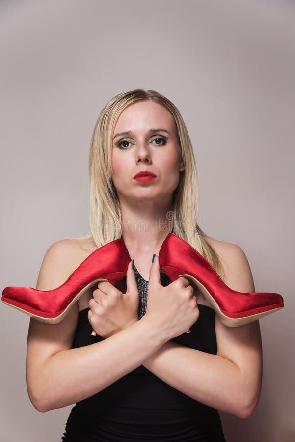 Kvinna som rymmer ett par av röda skor vertikalt royaltyfria bilder