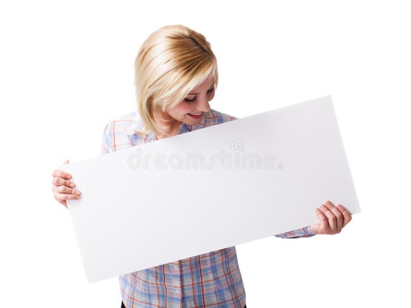 Kvinna som rymmer ett tomt vitt kort främst av henne arkivfoton