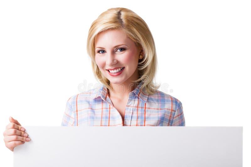 Kvinna som rymmer ett tomt vitt kort främst av henne royaltyfri foto