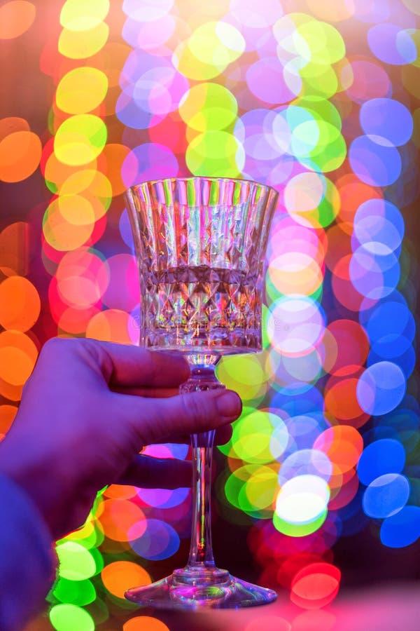 Kvinna som rymmer ett vinexponeringsglas på abstrakt färgrik bokehbakgrund Festlig, för jul eller för nytt år tema för beröm, royaltyfri fotografi