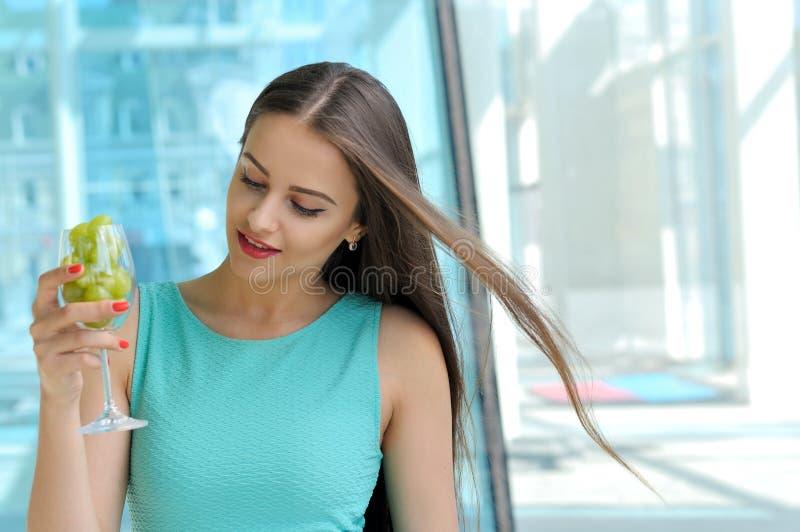 Kvinna som rymmer ett wineexponeringsglas royaltyfri foto