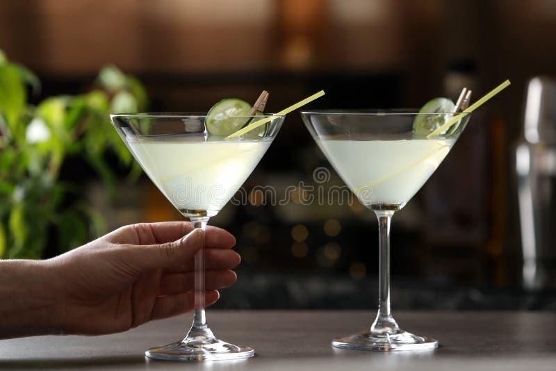 Kvinna som rymmer exponeringsglas av martini på stångräknaren royaltyfri bild