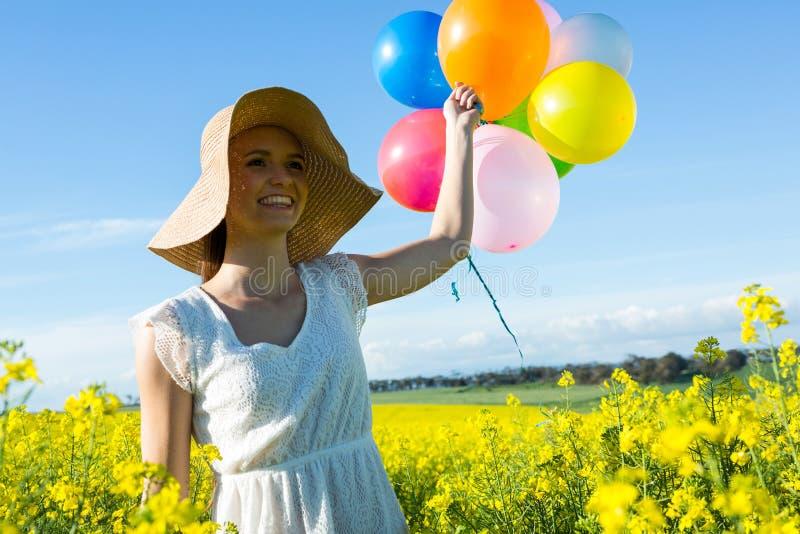 Download Kvinna Som Rymmer Färgrika Ballonger I Senapsgult Fält Arkivfoto - Bild av blomma, livsstil: 78725628