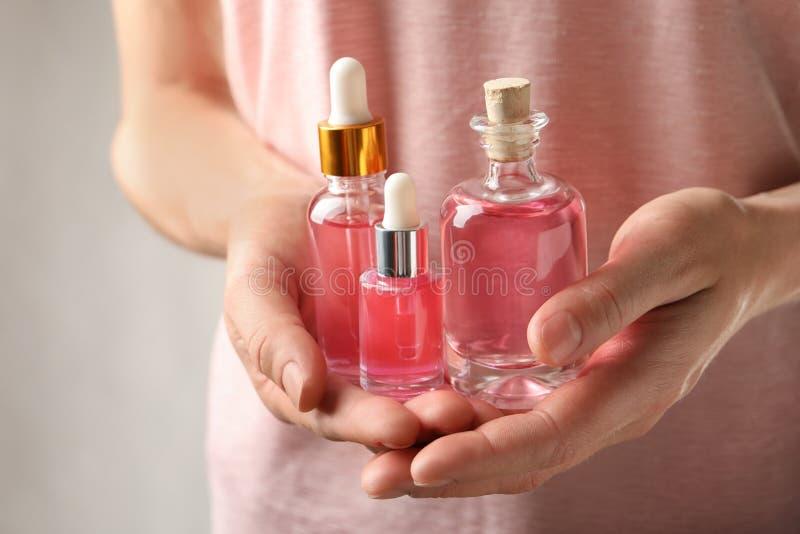 Kvinna som rymmer flaskor av rosa nödvändig olja i händer arkivfoto