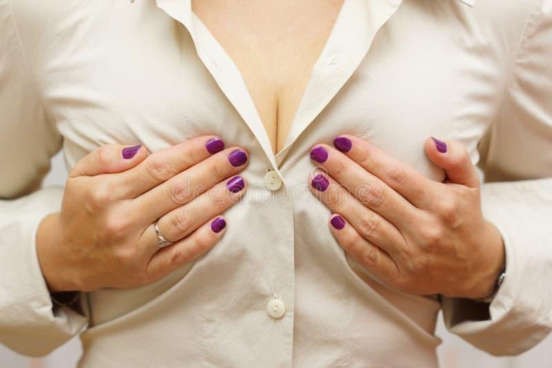 Kvinna som rymmer henne bröst arkivfoton