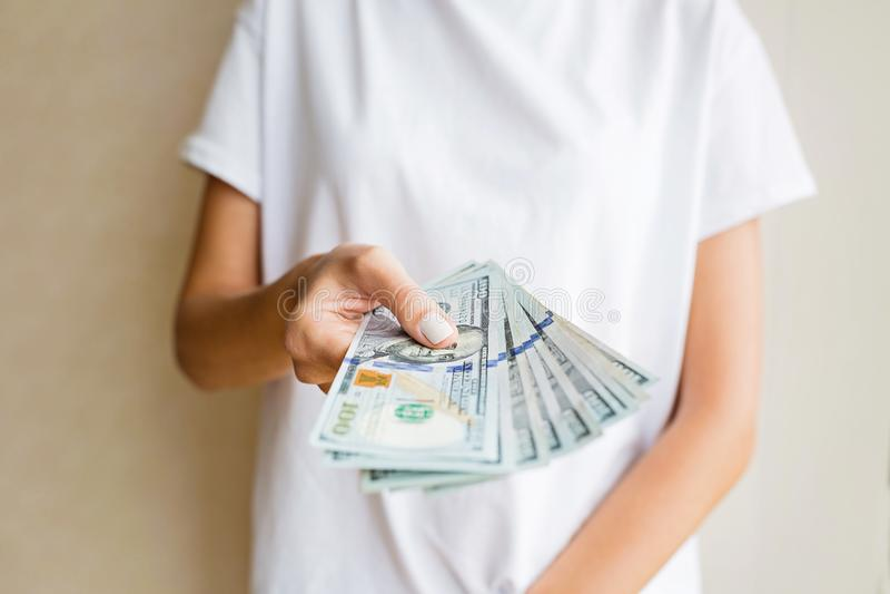 Kvinna som rymmer kassa hundra dollar räkningar på beige bakgrund finansiell aff?rsid? royaltyfri bild