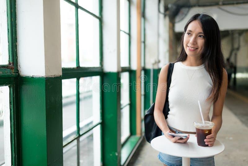 Kvinna som rymmer med is kaffe och ser ut ur fönster arkivfoto